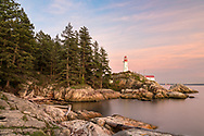 The Point Atkinson Lighthouse at the beginning of sunset at Lighthouse Park in West Vancouver, British Columbia, Canada.  Photographed from the rocks along the shore of Burrard Inlet and the Salish Sea at West Beach.The Point Atkinson Lighthouse was built in 1912 and is a National Historic Site in Canada.