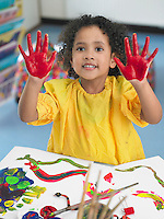 Girl finger painting in art class elevated view
