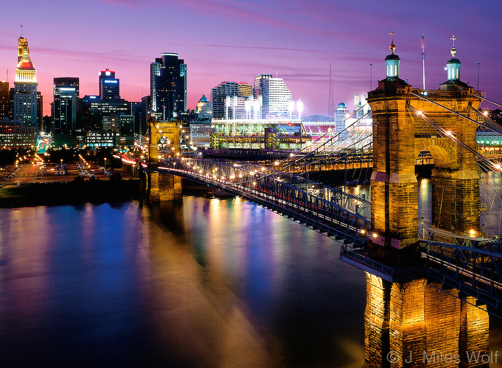 The colorful Cincinnati Skyline and the Roebling Suspension Bridge at night