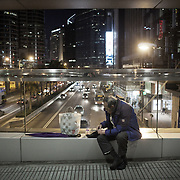 A man rests and sort out his right shoe on a walk way crossing a busy road in Central.<br />