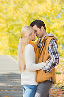 Couple kissing in park during autumn