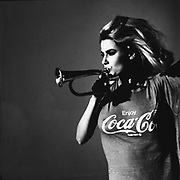 A woman in a Coca Cola T-shirt blowing a horn, UK, 1980's.