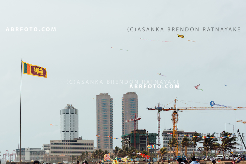 The Sri Lanka flag fluttering during a strong breeze at the Galle Face Green with the world trade centre buildings and colombo harbour shipping cranes in the background Colombo, Sri Lanka