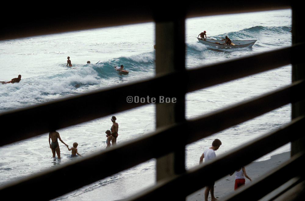 View of people at the beach through the boardwalk fence
