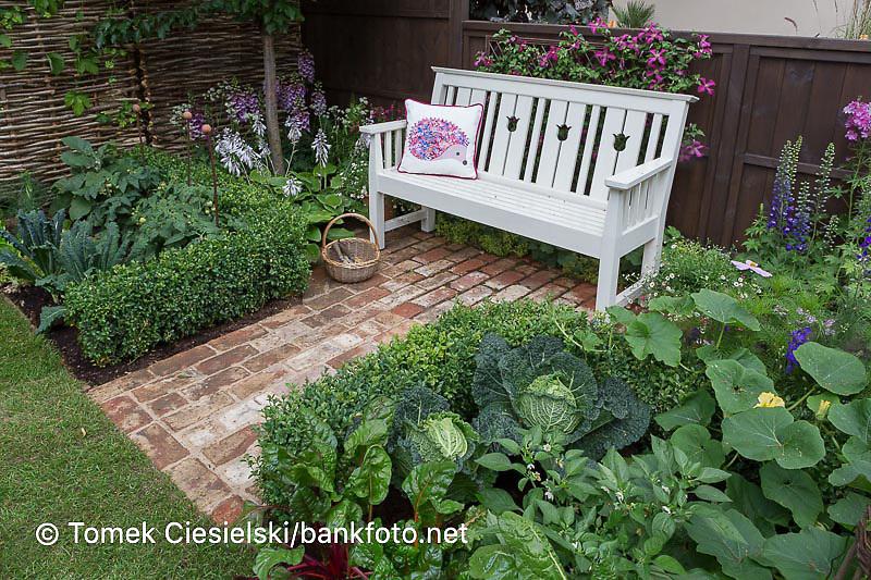 White romantic wooden bench set in small kitchen garden