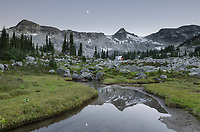 Moon and mountains reflected in creek, Marriott Basin, Coast Mountains British Columbia