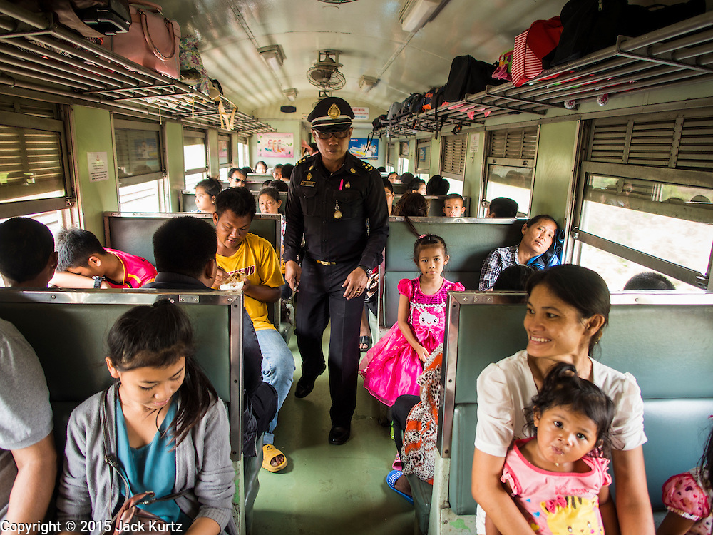 19 MARCH 2015 - AYUTTHAYA, AYUTTHAYA, THAILAND:   The conductor on the third class train from Ayutthaya to Bangkok check passengers' tickets. The train line from Bangkok to Ayutthaya was the first rail built in Thailand and was opened in 1892. The State Railways of Thailand (SRT), established in 1890, operates 4,043 kilometers of meter gauge track that reaches most parts of Thailand. Much of the track and many of the trains are poorly maintained and trains frequently run late. Accidents and mishaps are also commonplace. Successive governments, including the current military government, have promised to upgrade rail services. The military government has signed contracts with China to upgrade rail lines and bring high speed rail to Thailand. Japan has also expressed an interest in working on the Thai train system. Third class train travel is very inexpensive. Many lines are free for Thai citizens and even lines that aren't free are only a few Baht. Many third class tickets are under the equivalent of a dollar. Third class cars are not air-conditioned.   PHOTO BY JACK KURTZ