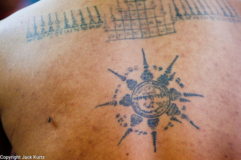 "Mar. 29, 2010 - NAKORN CHAI SRI, THAILAND:  A Sak Yent tattoo on a man's back at Wat Bang Phra about 30 miles from Bangkok in Nakhon Pathom province. The temple is famous for its tattooing monks who give people ""Sak Yent"" tattoos, a form of sacred tattooing practiced in Southeast Asian countries including Cambodia, Laos, and Thailand. The typical tattoo takes about 3,000 strikes to complete. When ready to begin, he will dip the tip of the needle into a mix of oil, probably palm oil, Chinese charcoal ink, and possibly snake venom. The monk dips the needle into the ink about every 30 seconds.  PHOTO BY JACK KURTZ"