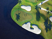 Aerial view of green on lake at Weston Hills Country Club, Weston, Florida with palm trees, sandtraps and golfers