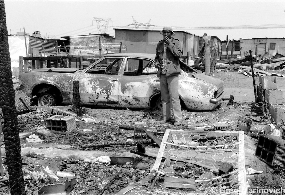 A man looks at the charred remains of his shack in Phola Park, Tokoza Oct 1990, on the East Rand some 20km East of Johannesburg. The neighbouring migrant workers' hostel was later destroyed in the clashes between Inkatha Freedom Party supporters and those of the African National Congress. (Photo by Greg Marinovich)