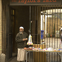 Asian stallholder selling plastic toys, Brick Lane market, London<br />