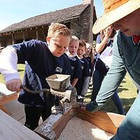 Tripp Estes, 9, grinds corn into feed that could be used for chickens and other animals during the pioneer days.