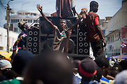 A group of young men dance to the music of loud speakers mounted on a moving trailer to amuse the crowd during the parade held on the occasion of the annual Oguaa Fetu Afahye Festival in Cape Coast, Ghana on Saturday September 6, 2008.
