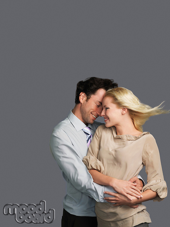 Smiling Young Couple embracing hair blowing in breeze