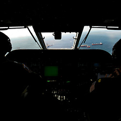 A view out of the cockpit of a C-144 U.S. Coast Guard Aircraft at the source of the BP Plc Deep Water Horizon oil spill site in the Gulf of Mexico off the coast of Louisiana, U.S., on Sunday, July 11, 2010. Oil is once again gushing freely into the Gulf of Mexico as BP Plc is in the process of changing out the cap from the leaking well and plans to have a new cap installed over the next few days that will allow for oil to be captured efficiently. Photographer: Derick E. Hingle/Bloomberg