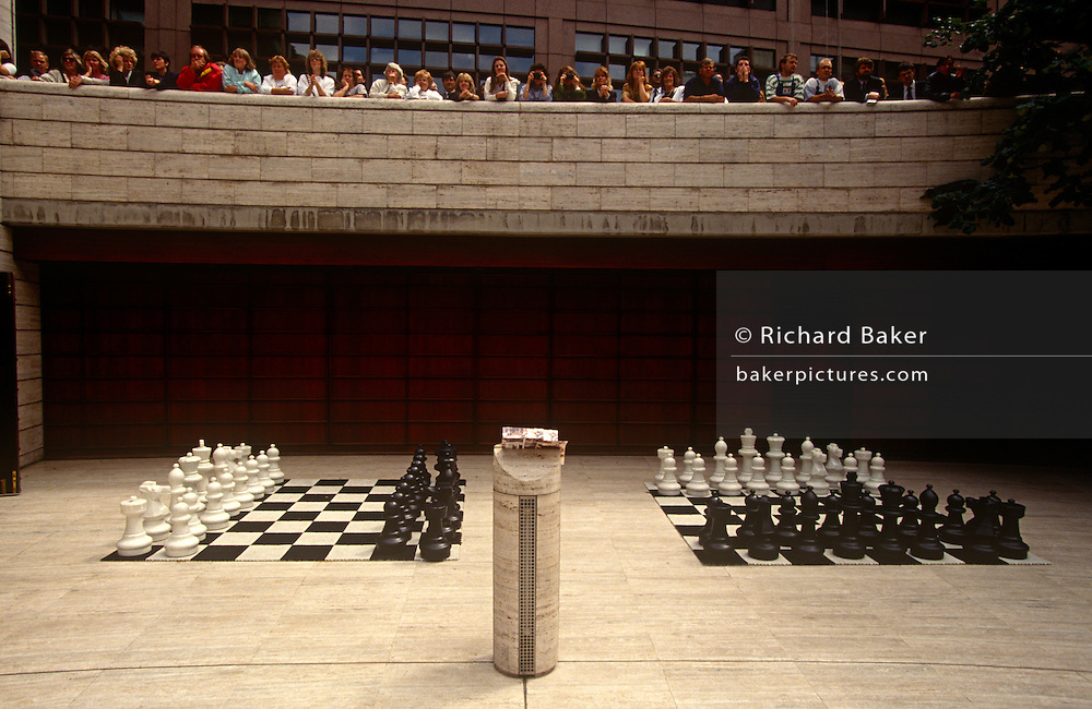 The pieces of two games of chess await players as a crowd on onlookers crowd above to see the lunchtime tournament at the Broadgate office plaza in the City of London. The first modern chess tournament was organized by Howard Staunton, a leading English chess player, and was held in London in 1851. It was won by the relatively unknown German Adolf Anderssen, who was hailed as the leading chess master, and his brilliant, energetic attacking style became typical for the time, although it was later regarded as strategically shallow. Broadgate is a large, 32-acre (13 ha) office and retail estate in the City of London, owned by British Land and the Blackstone Group and managed by Broadgate Estates.
