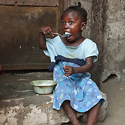 A girl eats while sitting on a doorstep in the West Point slum of Monrovia, Montserrado county, Liberia on Monday April 2, 2012.