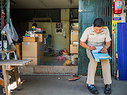 16 OCTOBER 2015 - BANGKOK, THAILAND:  A Thai government official completes eviction paperwork in for a resident in the Wat Kalayanamit neighborhood. Fifty-four homes around Wat Kalayanamit, a historic Buddhist temple on the Chao Phraya River in the Thonburi section of Bangkok, are being razed and the residents evicted to make way for new development at the temple. The abbot of the temple said he was evicting the residents, who have lived on the temple grounds for generations, because their homes are unsafe and because he wants to improve the temple grounds. The evictions are a part of a Bangkok trend, especially along the Chao Phraya River and BTS light rail lines. Low income people are being evicted from their long time homes to make way for urban renewal.   PHOTO BY JACK KURTZ