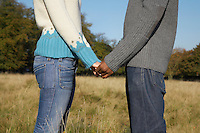 Couple standing in field holding hands mid section side view