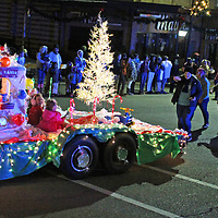 The Haney, English and Walker families walk and ride on their float during the Aberdeen Christmas parade.