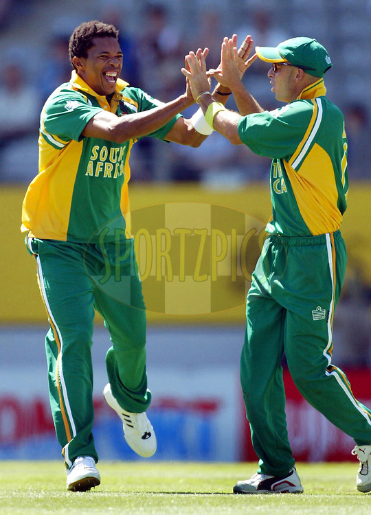13 February 2004, International one day cricket, Eden Park, Auckland, New Zealand. Match 1 in series of 6, New Zealand vs South Africa..South African fast bowler Makhaya Ntini celebrates with Herschelle Gibbs after dismissing New Zealand batsman Hamish Marshall who was caught behind by Mark Boucher for 7 runs.At the end of 50 overs and at the tea break New Zealand were 225 for the loss of 8 wickets..Please credit: Andrew Cornaga/Photosport