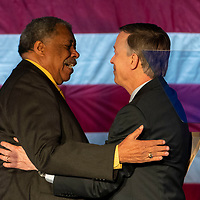 Former Denver Mayor Wellington Webb hugs Democratic presidential candidate and former Colorado Governor John Hickenlooper while introducing Hickenlooper for a presidential campaign rally at the Greek Amphitheater in Denver's Civic Center Park on Thursday, March 7, 2019. Photo by Andy Colwell, special to the Colorado Sun
