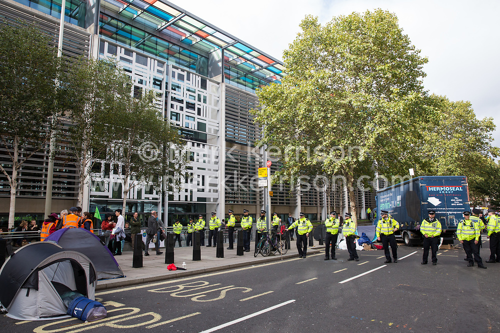 London, UK. 8 October, 2019. Metropolitan Police officers form a cordon in front of climate activists from Extinction Rebellion blocking Marsham Street in front of the Home Office on the second day of International Rebellion protests to demand a government declaration of a climate and ecological emergency, a commitment to halting biodiversity loss and net zero carbon emissions by 2025 and for the government to create and be led by the decisions of a Citizens' Assembly on climate and ecological justice.
