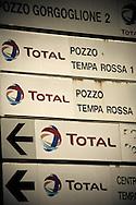 Corleto Perticara (PZ) 17.02.2009, Italy - Tempa Rossa - Speranze e realtà del giacimento Total in Basilicata. Il  giacimento petrolifero si estende in superficie per circa 30.000 ettari di terreno boschivo a nord-est dell'abitato, ampiamente sfruttato già dal 2001 nella produzione di energia eolica. Il 28 gennaio 2008 il comune di Corleto Perticara, nella persona del suo sindaco, avvocato Paolo Pietro Montano e Total Italia S.p.A. nella persona del suo amministratore delegato per il settore Esplorazione e Produzione, Dott. Lionel Levha, hanno siglato un Patto storico per la concessione dei diritti di superficie necessari alla realizzazione di un centro olio in località Tempa Rossa, a quattro Km in linea d'aria dal centro abitato, per un tempo pari a 99 anni. La coltivazione di idrocarburi, che a a pieno regime comporterà l'estrazione di 50.000 barili di greggio al giorno, gas naturale per 250.000 m2, GPL per 267 tonnellate e zolfo per 60 tonnellate, avrà inizio entro l'anno 2011. Le riserve sono stimate intorno ai 420 milioni di barili equivalenti. NELLA FOTO: Gruppo di indicazioni stradale Total.