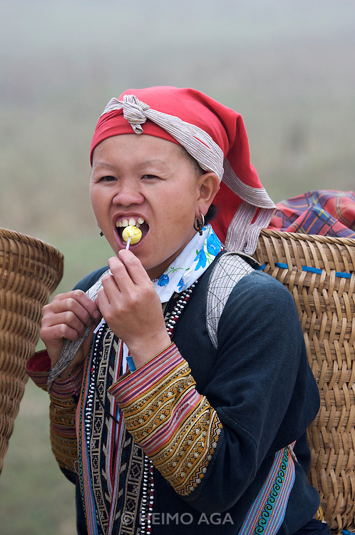 Hilltribe villages around Sapa. Red Dzao woman with lollipop.