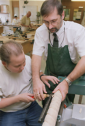 Technical instructor in occupational therapy session instructing male patient on how to carve table leg in hospital workshop in order to improve muscle strength in preparation for returning to work,