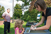 Volunteer Chelsea Philipp (Right) helps Mackenzie Lee, 5, develop a cyanotype picture outside the Kennedy Museum of Art at Fall Family Day on Saturday, September 29.