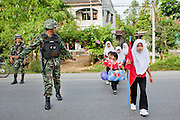 "Sept. 27, 2009 -- PATTANI, THAILAND: Thai soldiers provide security for children walking to the Gahong School in Pattani, Thailand, Sept 27. Schools and school teachers have been frequent targets of Muslim insurgents in southern Thailand and the army now provides security at many government schools.  Thailand's three southern most provinces; Yala, Pattani and Narathiwat are often called ""restive"" and a decades long Muslim insurgency has gained traction recently. Nearly 4,000 people have been killed since 2004. The three southern provinces are under emergency control and there are more than 60,000 Thai military, police and paramilitary militia forces trying to keep the peace battling insurgents who favor car bombs and assassination.  Photo by Jack Kurtz / ZUMA Press"