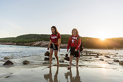 Two teenagers walk barefoot on Sand Beach after a hike in Maine's Acadia National Park.