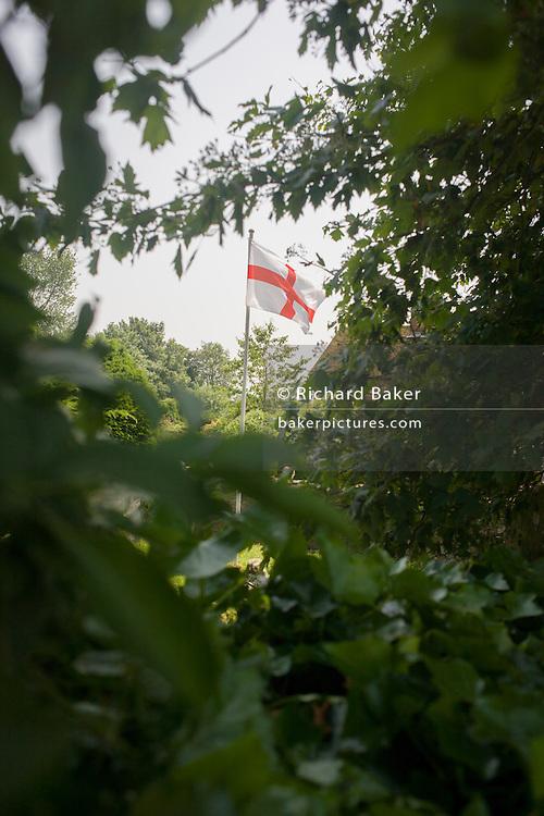 The English flag flies in the churchyard of St Dunstan church, West Peckham, Kent.