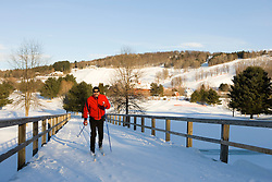 A man cross-country skiing (track skiing) on a groomed trail in Quechee, Vermont. Model Release.