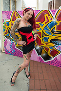 Garden City, New York, USA. September 13, 2015. ALECIA REY, of Bayshore, poses in front of a colorful painted mural by contemporary artist Matt Thomas, street name of SOLE4, of Amityville, at the United Ink Flight 915 Tattoo convention at the Cradle of Aviation Museum in Long Island.