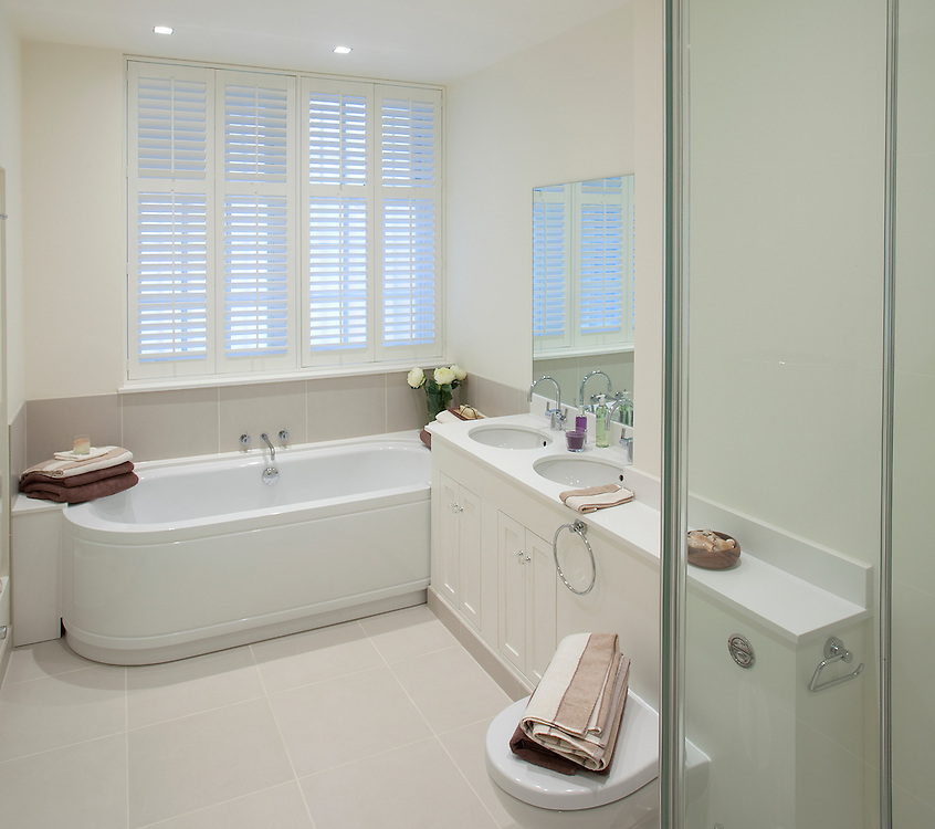 bathroom interior in showhouse with white bath sink toilet towels and shutters