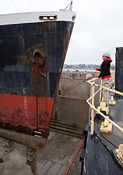 A dock worker stands near the first ship to be recycled by Allied Defense Recycling.  Hundreds of attendees from throughout the region came to mark the official re-opening of the Mare Island Dry Docks.