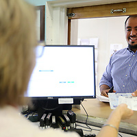 Neft Jimenez, of Tupelo, is handed his car tag by Angie Garrett, a Deputy Clerk in the Lee County Tax Collectors Office in Tupelo on Wednesday morning.