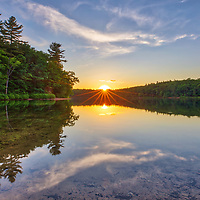 Sunset reflection at Walden Pond in Concord showing a magical mixture of trees and orange hues. I was on my way to the Minute Man National Historic Park when I realized that there might be spectacular sunset light to be photographed. I quickly pulled over, made my way to the banks of this famous pond that Thoreau ones called home, and took a few photographs. <br />