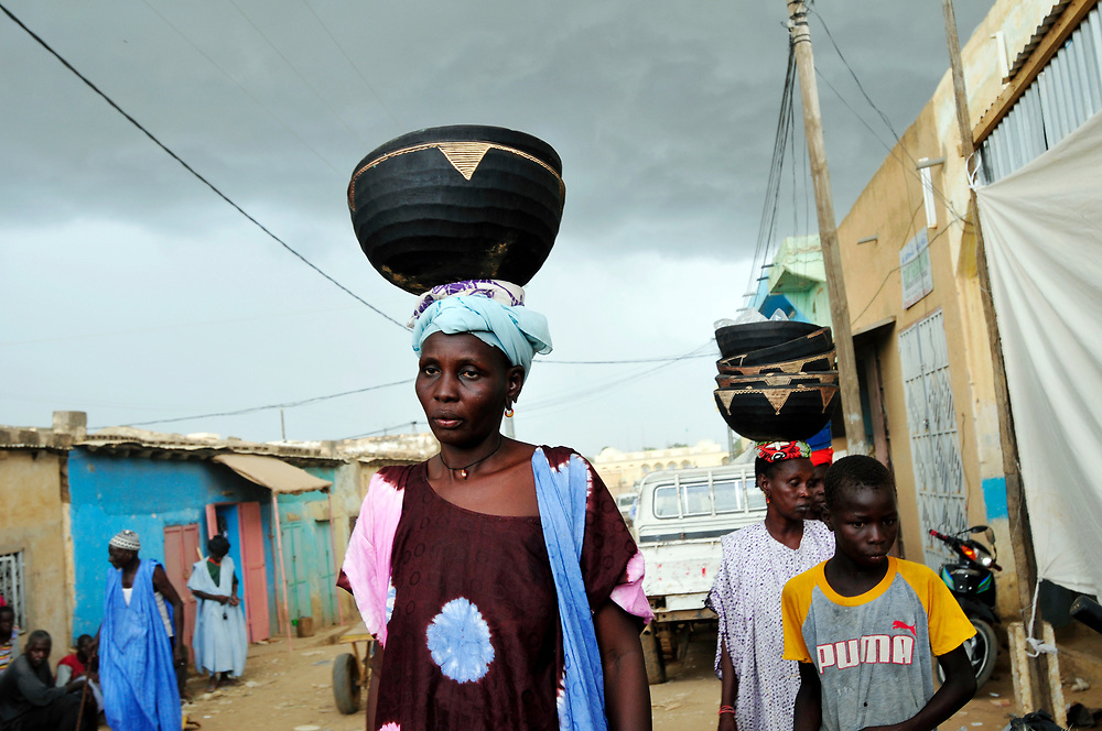 A woman walks through the market under a sky heavily laden with rain clouds. Life in the Sahel depends on and revolves around the cycles rainy seasons and dry seasons. If the rains fail or are insufficient, crops also fail or harvests are not abundant enough to feed the population during the long dry season months of scorching sun and heat. Climate change has caused prolonged drought and erratic rains across the Sahel in recent years, exacerbating food insecurity and poverty throughout the region.<br /> S&eacute;libaby, Mauritania. 06/09/2010.