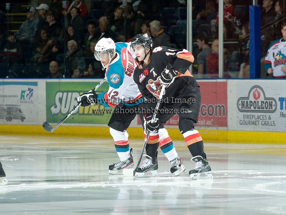 KELOWNA, CANADA, JANUARY 1: Tyrell Goulbourne #12 of the Kelowna Rockets is checked by Jimmy Bubnick #14 of the Calgary Flames as the Calgary Hitmen visit the Kelowna Rockets on January 1, 2012 at Prospera Place in Kelowna, British Columbia, Canada (Photo by Marissa Baecker/Getty Images) *** Local Caption ***