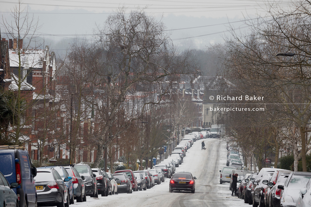 A car descends an icy minor road in the south London borough of Herne Hill, Lambeth during the bad weather covering every part of the UK and known as the 'Beast from the East' because Siberian winds and very low temperatures have blown across western Europe from Russia, on 1st March 2018, in Lambeth, London, England