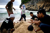 Aceh teens hang out at the beach as two veiled girls walk past them along the shore at Lampu'uk Beach, a small fishing village outside of Banda Aceh, Indonesia, on Sunday, Nov. 22, 2009. Tsunami waves travelled 7 km inland, killing one out of four people, and devastating the entire community. Achenese have now returned to the beaches were they spend time.