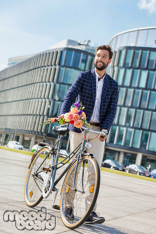 Portrait of young attractive businessman standing with his bicycle while holding boquet of flowers