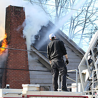 A tupelo fireman monitors the water floow and position of the ladder as the department fights a ouse fire on Walker Street Monday morning.