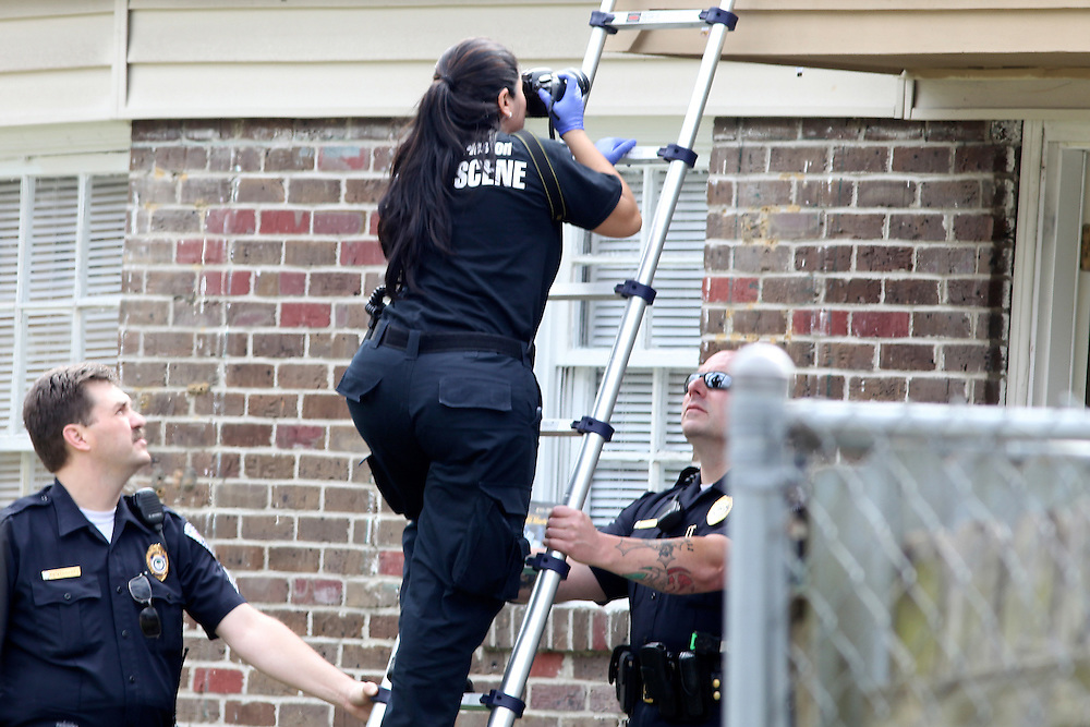 ANDREW KNAPP/STAFF -- March 18, 2013 -- A North Charleston police investigator photographs a bullet hole in a house at 5421 Torgerson St. after several gunshots were fired Monday afternoon.