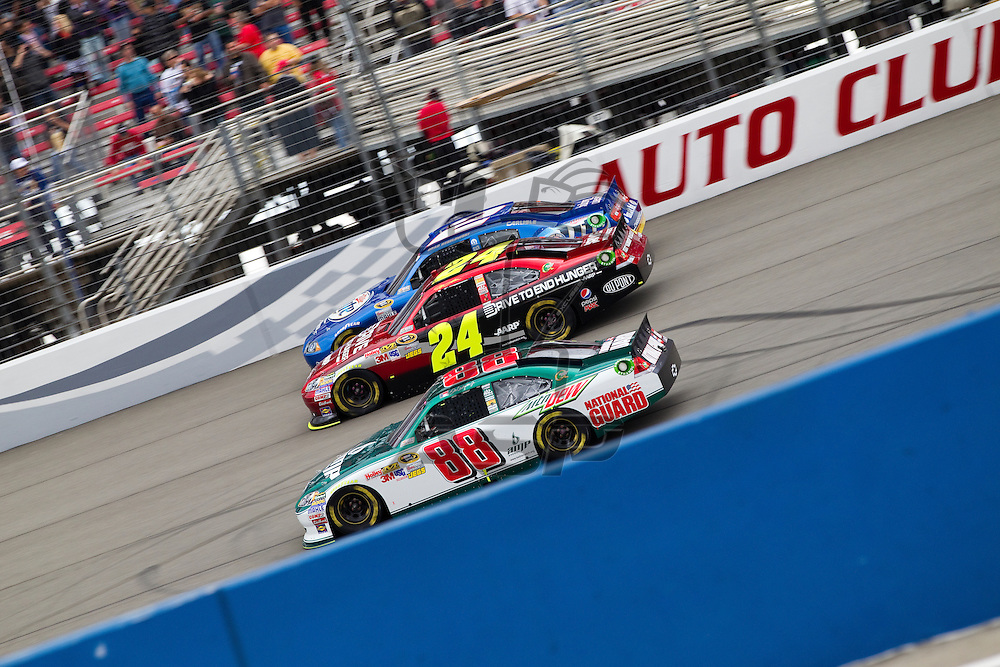 FONTANA, CA - MAR 27, 2011:  Dale Earnhardt, Jr. (88), Jeff Gordon (24), and Brad Keselowski (2) race for position down the front stretch during the Auto Club 400 race at the Auto Club Speedway in Fontana, CA.