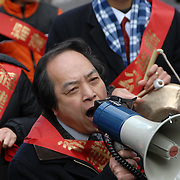 Chinese speaker marching in parade with bull horn.  Ethnic pride and tradition in the Chinese Lunar New Year Celebration Parade in New York Chinatown,The Year of the Rat.