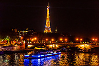 A bateau mouche on the River Seine with Eiffel Tower in background, Paris, France.